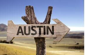 "Hot day in Austin with a wooden sign that reads ""Austin""."