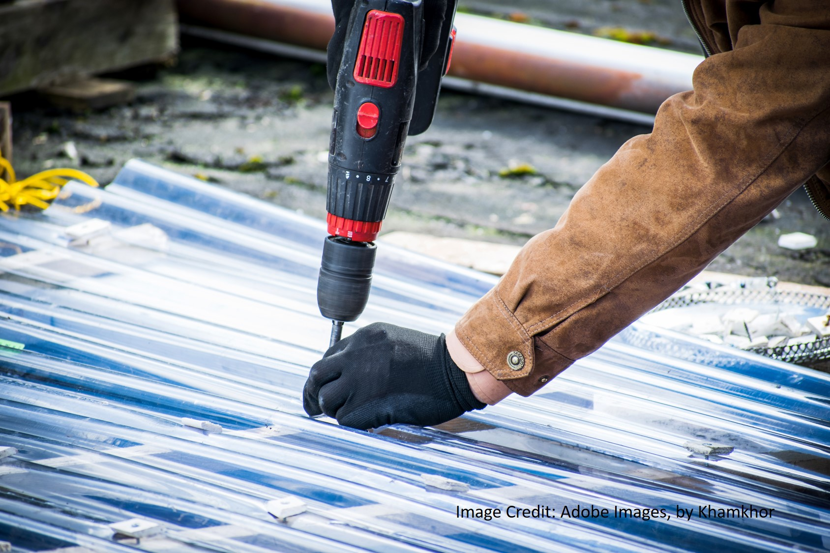 a metal roofer replaces screws on a corrugated metal roof